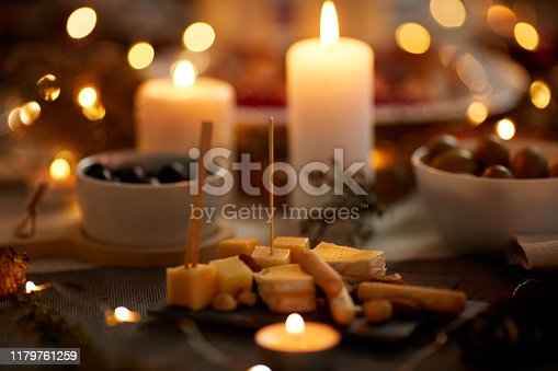 Close-up of cheese appetizer on the dining table with candles ready for dinner