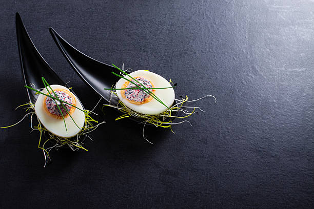 appetizer on fingerspoon egg with caviaron black background. - food styling stock photos and pictures