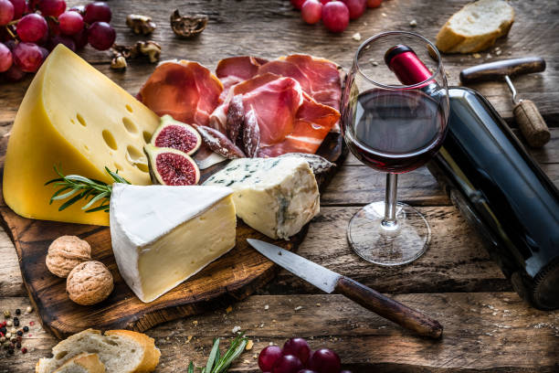 appetizer: red wine, cheese and cured ham on rustic wooden table - cheese imagens e fotografias de stock