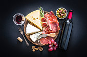 Appetizer: top view of a composition of red wine bottle, wineglass, a cutting board with various cheeses and cured ham arranged at the center of a black background. Some grapes, olives, nuts and a corkscrew complete the composition. Predominant colors are red and black. XXXL 42Mp studio photo taken with Sony A7rii and Sony FE 90mm f2.8 macro G OSS lens