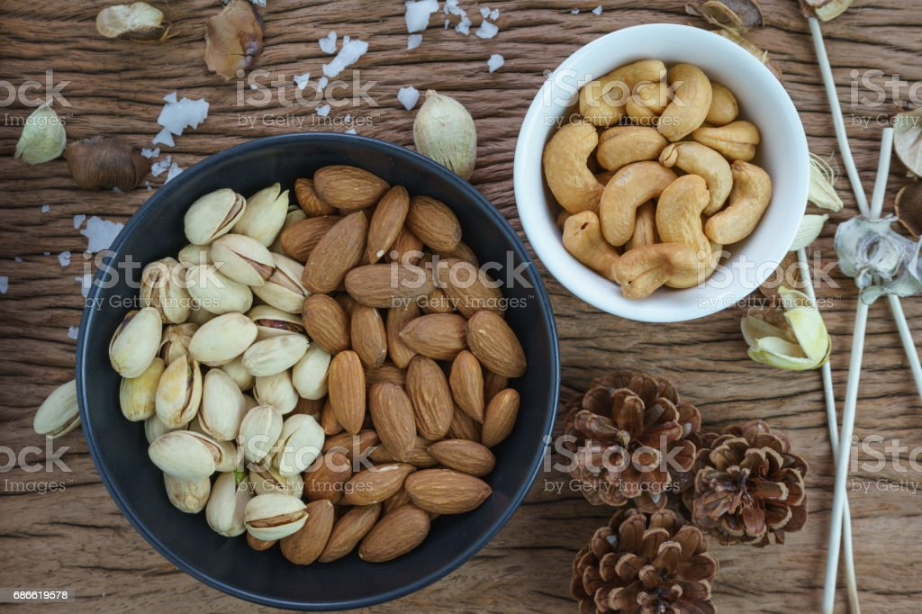 appetizer roasted healthy delicious salt pistachios, cashew nuts and almonds food in black bowl on wooden table background royalty-free stock photo