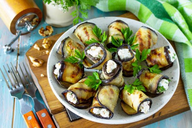 전채 박제 가지. 나무 부엌 테이블에 접시에 페타 치즈와 견과류와 구운 가지 롤. 스톡 사진