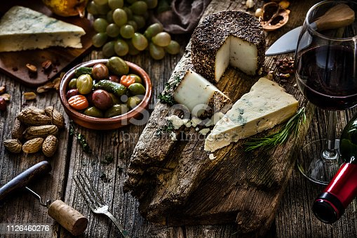 Appetizer or snack themes. High angle view of a rustic wooden table served with various cheeses and a selection of olives. A wineglass is visible at the right. Some fruits like grapes, figs and pears complete the composition. A corkscrew and a wine bottle are included in the composition. Predominant color is brown. Low key DSRL studio photo taken with Canon EOS 5D Mk II and Canon EF 70-200mm f/2.8L IS II USM Telephoto Zoom Lens