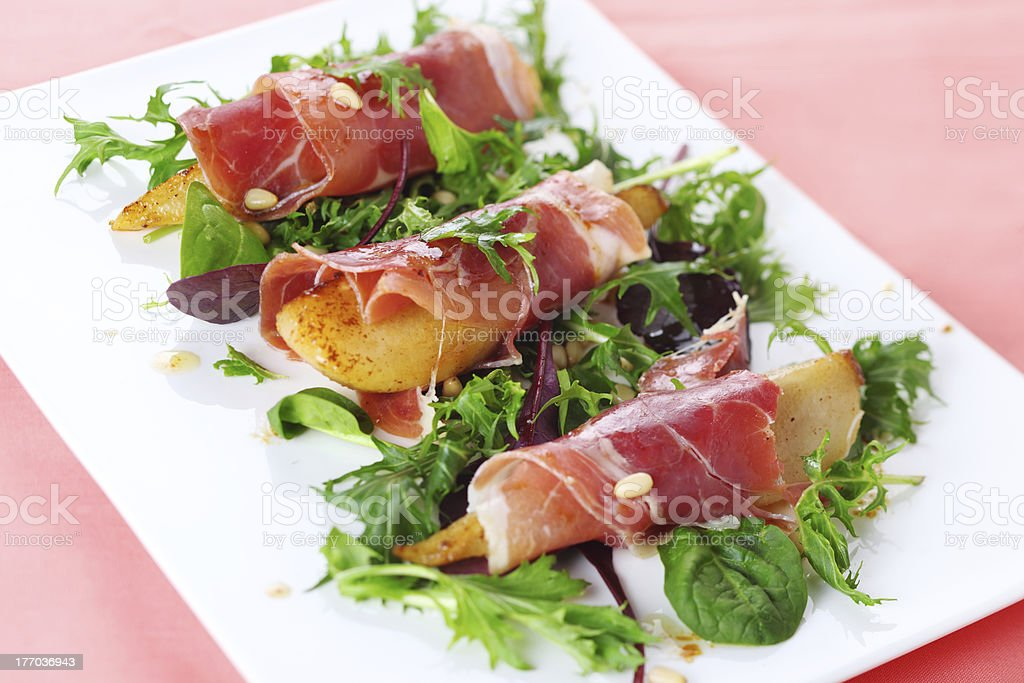 Appetizer with caramelized pears, walnuts and prosciutto stock photo