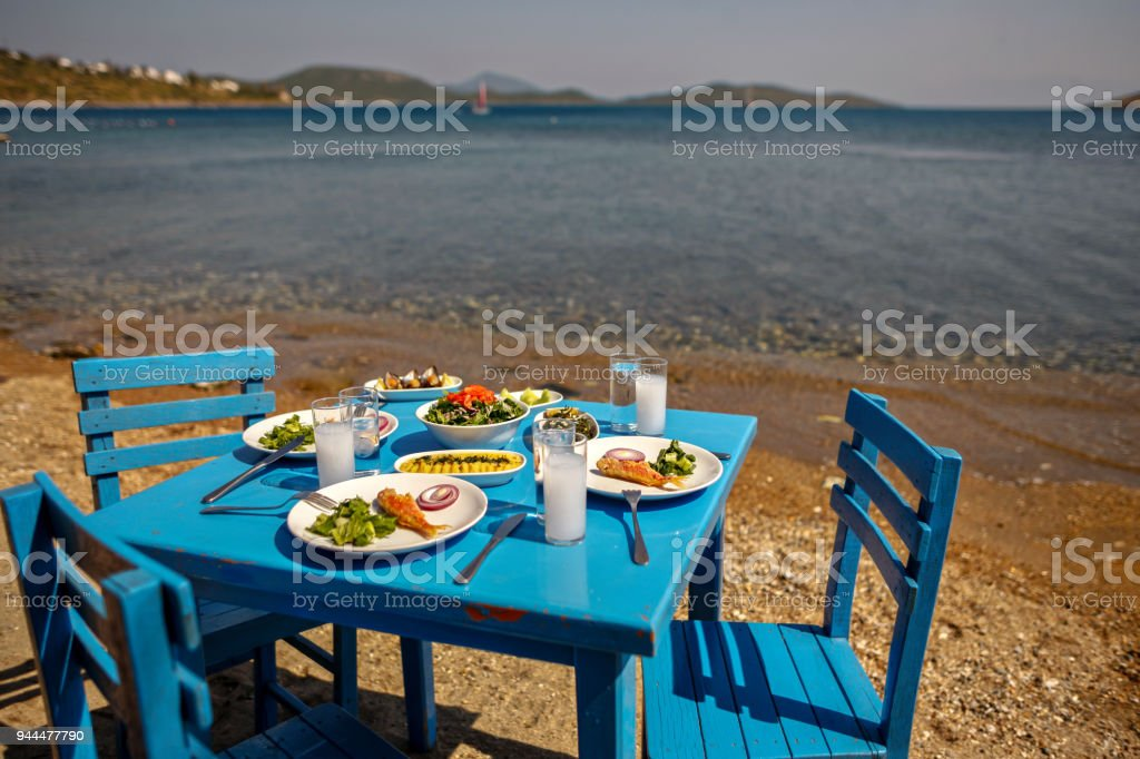 Appetizers and Raki or Ouzo Served on a Blue Table on the Beach Besides Beautiful Sea View - foto stock