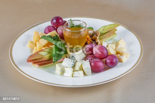 Appetizers. Plate with different kinds of cheese garnished with apples, grape and honey