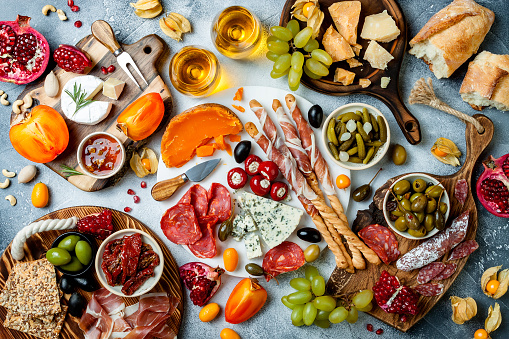 istock Appetizers table with antipasti snacks and wine in glasses. Authentic traditional spanish tapas set, cheese and meat platter over grey concrete background. Top view 1097932504