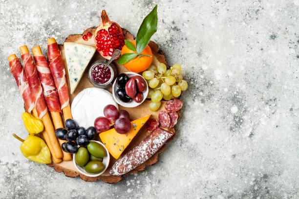 vorspeisen-tisch mit antipasti-snacks. käse und fleisch auswahl board über graue konkreten hintergrund. ansicht von oben flach legen - salami vorspeise stock-fotos und bilder