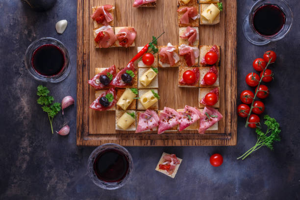 Appetizers table with italian antipasti snacks and wine in glasses. Brushetta or authentic traditional spanish tapas set, cheese variety board over grey concrete background. Top view, flat lay stock photo