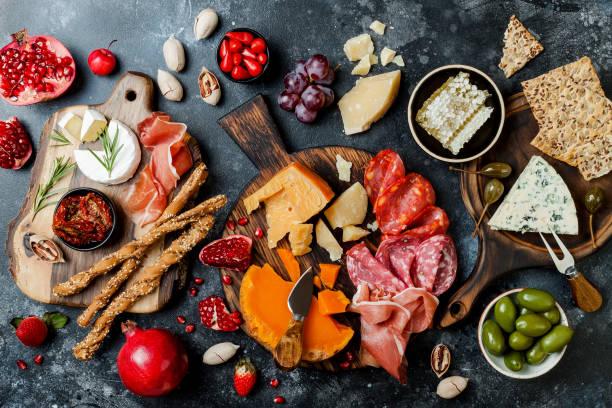 Vorspeisen mit italienischen Antipasti-Snacks. Brushetta oder authentische traditionelle spanische Tapas-Set, Käse-Sorten mit schwarzem Steingrund. Top Aussicht, flach gelegen – Foto