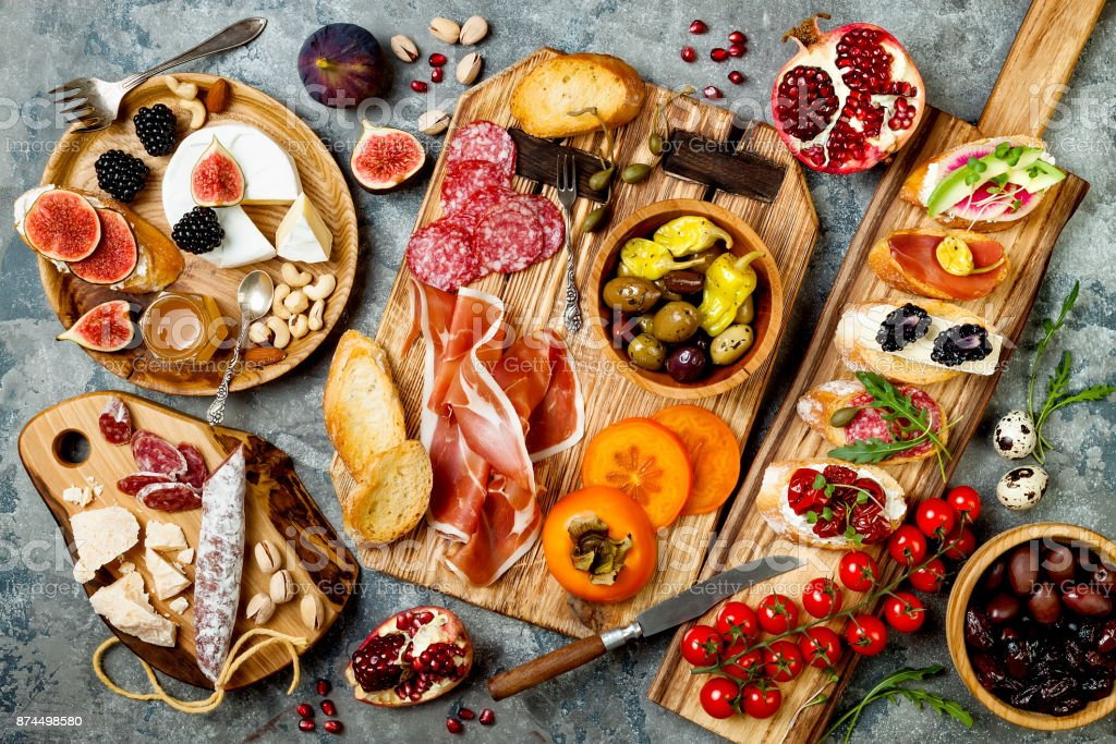 Appetizers table with italian antipasti snacks. Brushetta or authentic traditional spanish tapas set, cheese variety board over grey concrete background. Top view, flat lay - foto stock