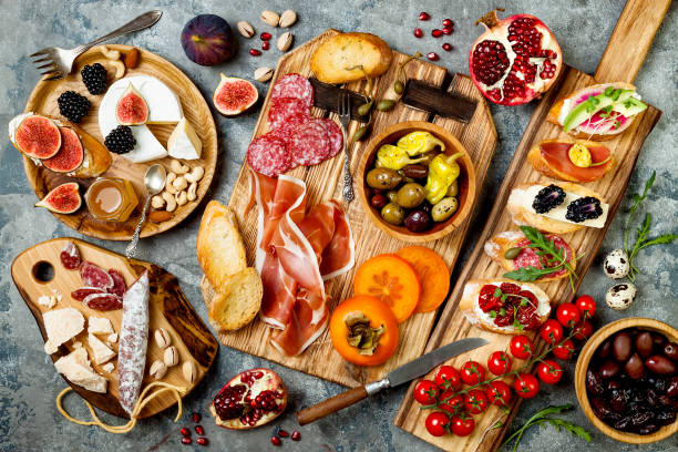 Appetizers table with italian antipasti snacks. Brushetta or authentic traditional spanish tapas set, cheese variety board over grey concrete background. Top view, flat lay stock photo