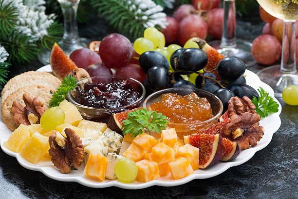 appetizers to the holiday - cheeses, fruits and jams, closeup - aufstrich weihnachten stock-fotos und bilder