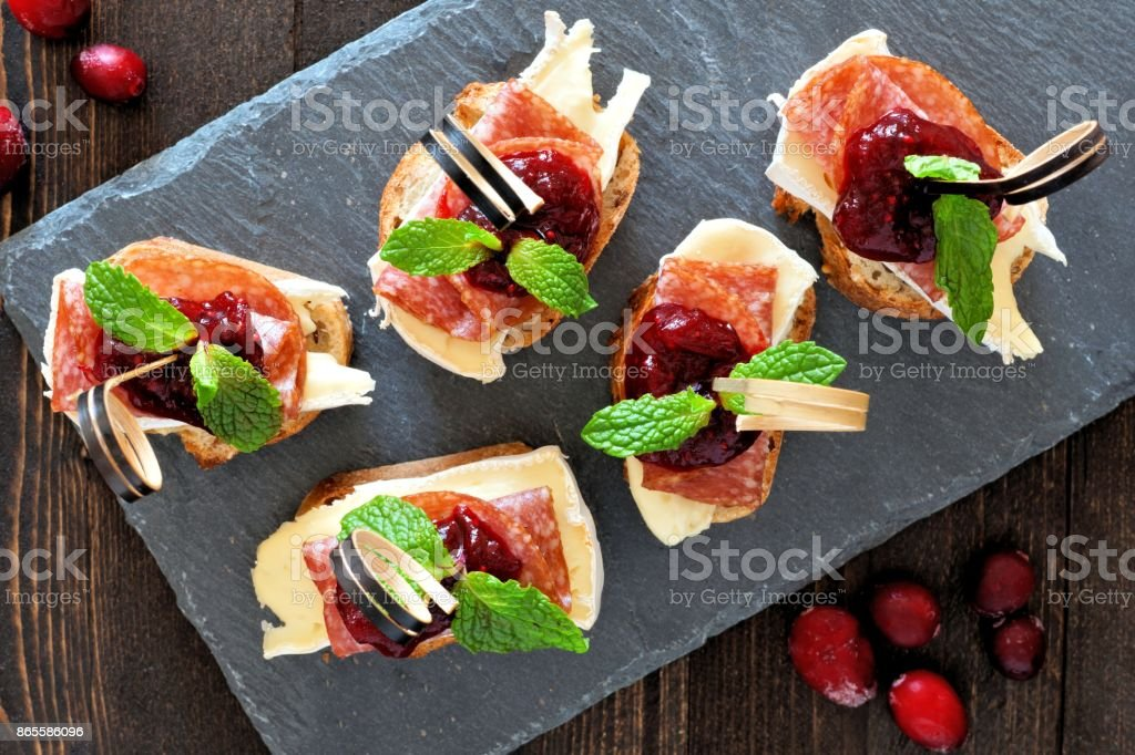 Appetizers with cranberry sauce above on a slate server stock photo