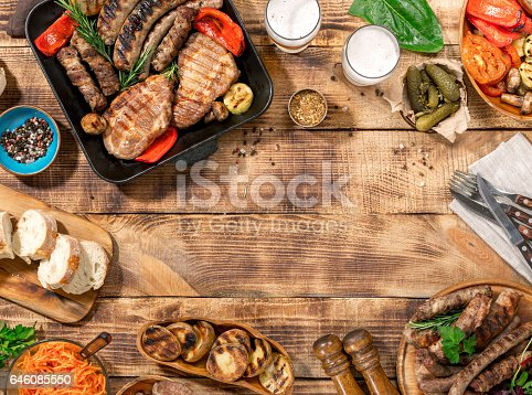 657146780 istock photo Appetizing barbecued steak, sausages and grilled vegetables on a wooden picnic table with copy space 646085550