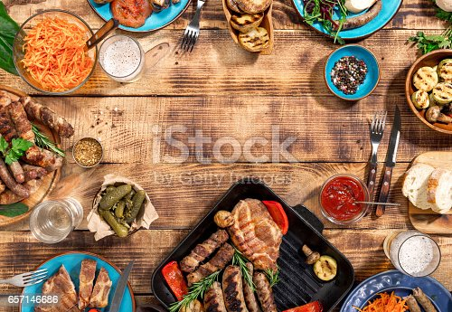 istock Appetizing barbecued steak, sausages and grilled vegetables on a wooden picnic table with copy space 657146686