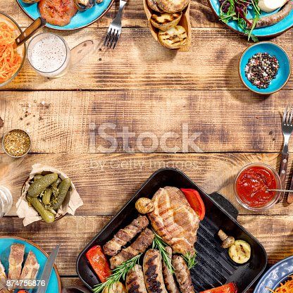 657146780 istock photo Appetizing barbecued steak, sausages and grilled vegetables on a wooden picnic table 874756876