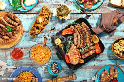 657146780 istock photo Appetizing barbecued steak, sausages and grilled vegetables on wooden blue picnic table 874754518