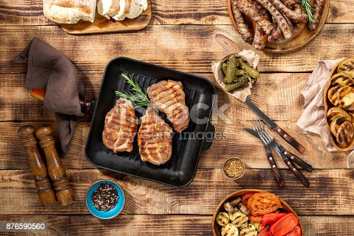 657146780 istock photo Appetizing barbecued steak, sausages and grilled vegetables on wooden picnic table 876590560