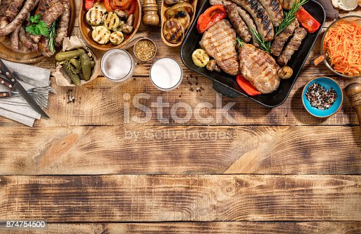 657146780 istock photo Appetizing barbecued steak, sausages, beer and grilled vegetables on wooden picnic table 874754500