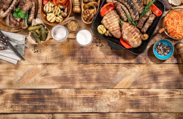 Appetizing barbecued steak, sausages, beer and grilled vegetables on wooden picnic table stock photo