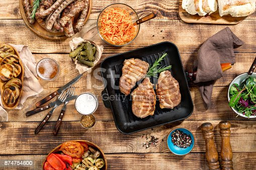 657146780 istock photo Appetizing barbecued steak, sausages, beer and grilled vegetables on wooden picnic table, top view 874754600