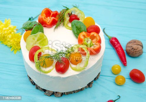 istock Appetizing cake with chicken meat, eggs and salad. Snack unsweetened cake. Wooden board with hot peppers and tomatoes. 1182490338