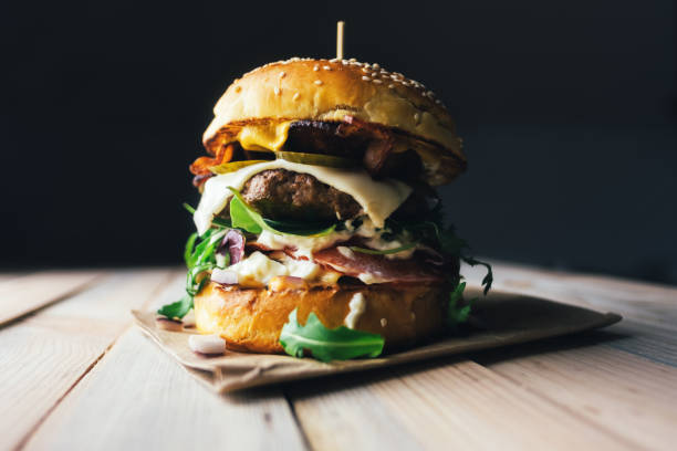 appetizing cheeseburger on wooden table. - cheeseburger стоковые фото и изображения