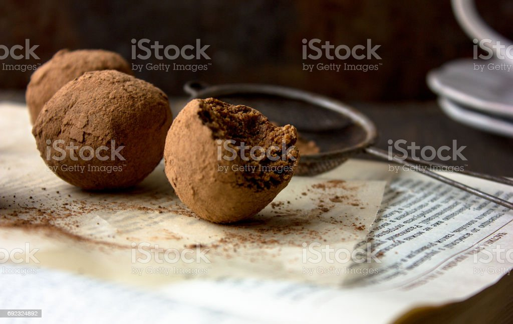 Appetizing chocolate 'potato' cake on an old vintage book background with cup of cofee stock photo