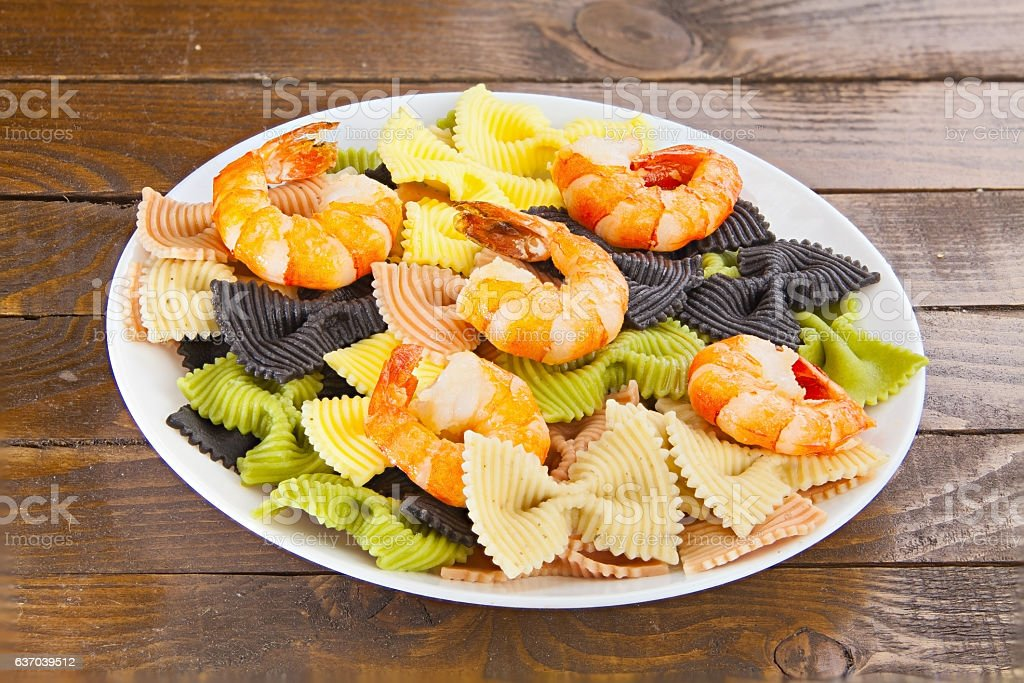 appetizing colored farfalle pasta with chrimp stock photo