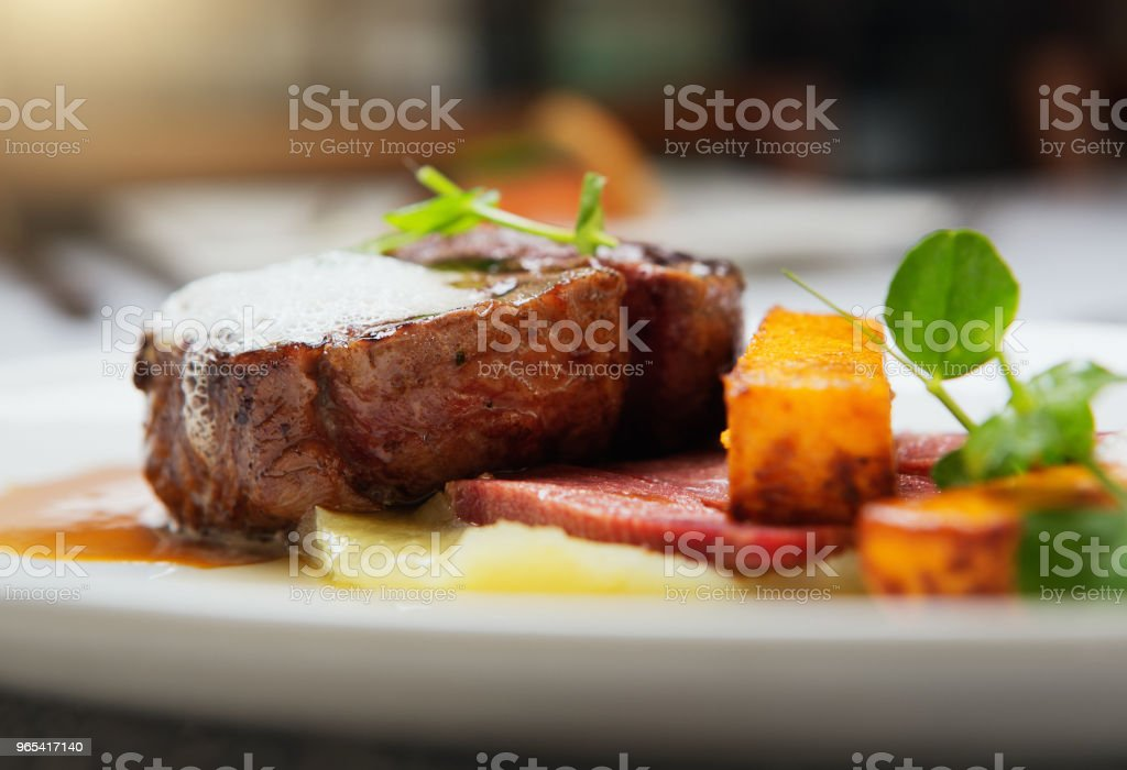 Appetizing fillet steak with gourmet accompaniments in restaurant zbiór zdjęć royalty-free
