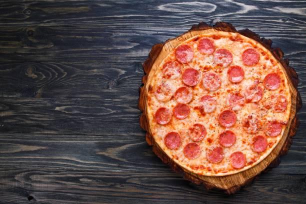 Appetizing freshly baked pepperoni pizza served on chopped wood, stock photo