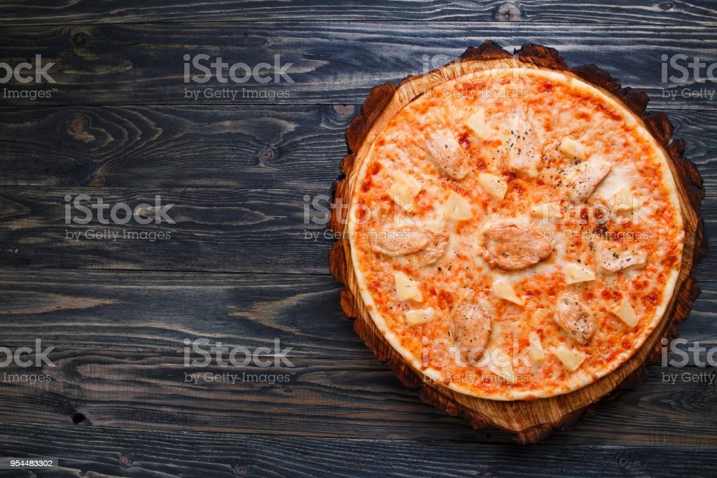 Appetizing freshly baked pizza with chicken and pineapple served stock photo