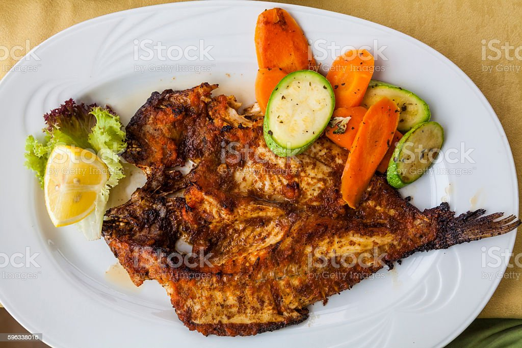 Appetizing grilled fish with vegetables and lemon. royalty-free stock photo