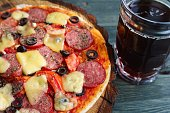 Appetizing homemade pizza with salami, cheese and olives and mug of stout, close up. Beer snacks concept