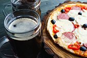 Appetizing homemade pizza with salami, mozzarella and olives and two mugs of stout, close up. Beer snacks concept
