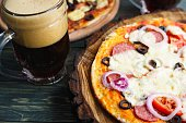 Appetizing homemade pizza with salami, mozzarella and olives and two mugs of foaming stout, close up. Beer snacks concept