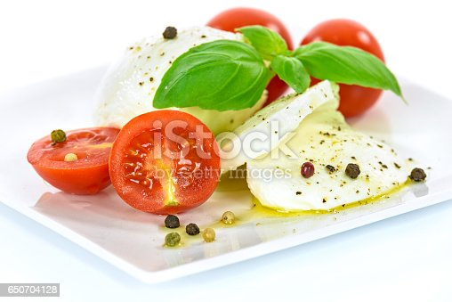 Delicacy of Italian cuisine - mozzarella cheese with basil leaves and baby tomatoes, flavored with olive oil and pepper