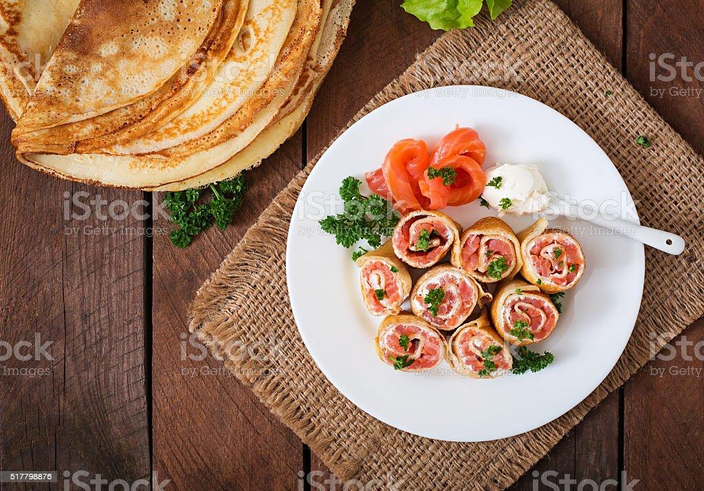 Appetizing pancakes with salmon and cream cheese 'Philadelphia'. Top view stock photo