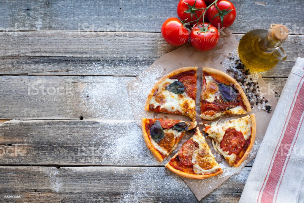 Appetizing pizza margarita on a wooden table in daylight. Vegetarian dish. Top view 免版稅 stock photo