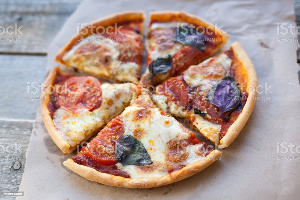 Appetizing pizza margarita on a wooden table in daylight. Vegetarian dish. Top view royalty-free 스톡 사진