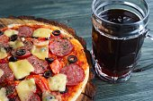 Appetizing pizza with salami, mozzarella and olives and mug of stout, close up. Beer snacks concept