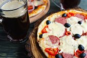 Appetizing pizza with salami, mozzarella and olives and two mugs of foaming stout, close up. Beer snacks concept