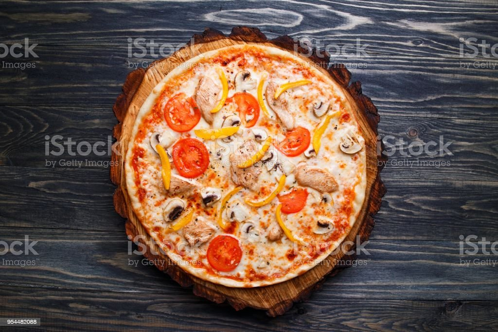 Appetizing pizza with tomato, chicken, paprika and mushrooms, to stock photo