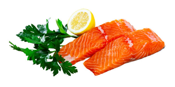 Appetizing raw salmon fillet with lemon and greens Background with appetizing raw salmon fillet with lemon and greens before cooking. Isolated over white background atlantic salmon stock pictures, royalty-free photos & images