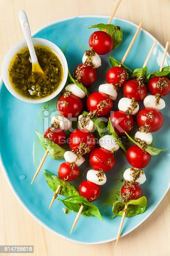 istock Appetizing vegetarian kebabs from cherry tomatoes and mini mozzarella in two kinds of basil and oregano sauce as a snack 814758618