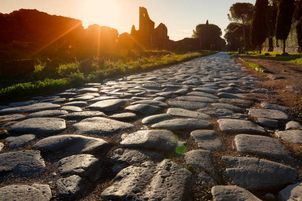 Appian Way Roma, italy - October 23, Stones of the road said Basolato at sunset ancient rome stock pictures, royalty-free photos & images