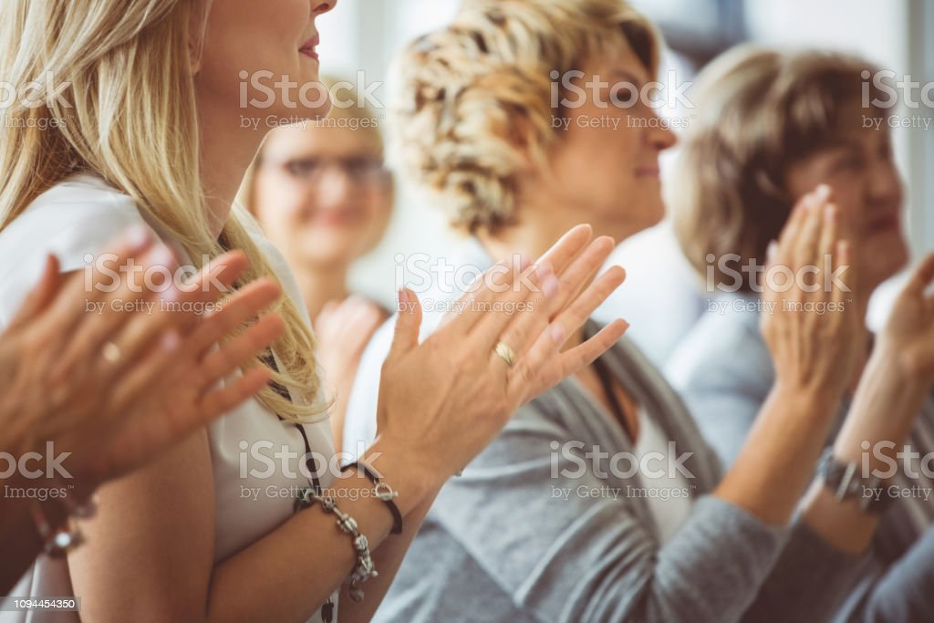 Applauding at seminar Group of women clapping hands during seminar. Audience applauding for the speaker. Achievement Stock Photo