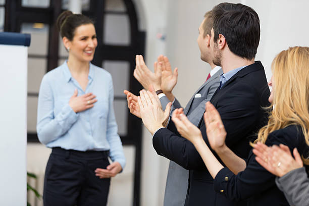 Applauding fsuccessful presentationor Business people smiling and applauding after a sucessfull presentation, businesswoman thanking them alongside stock pictures, royalty-free photos & images