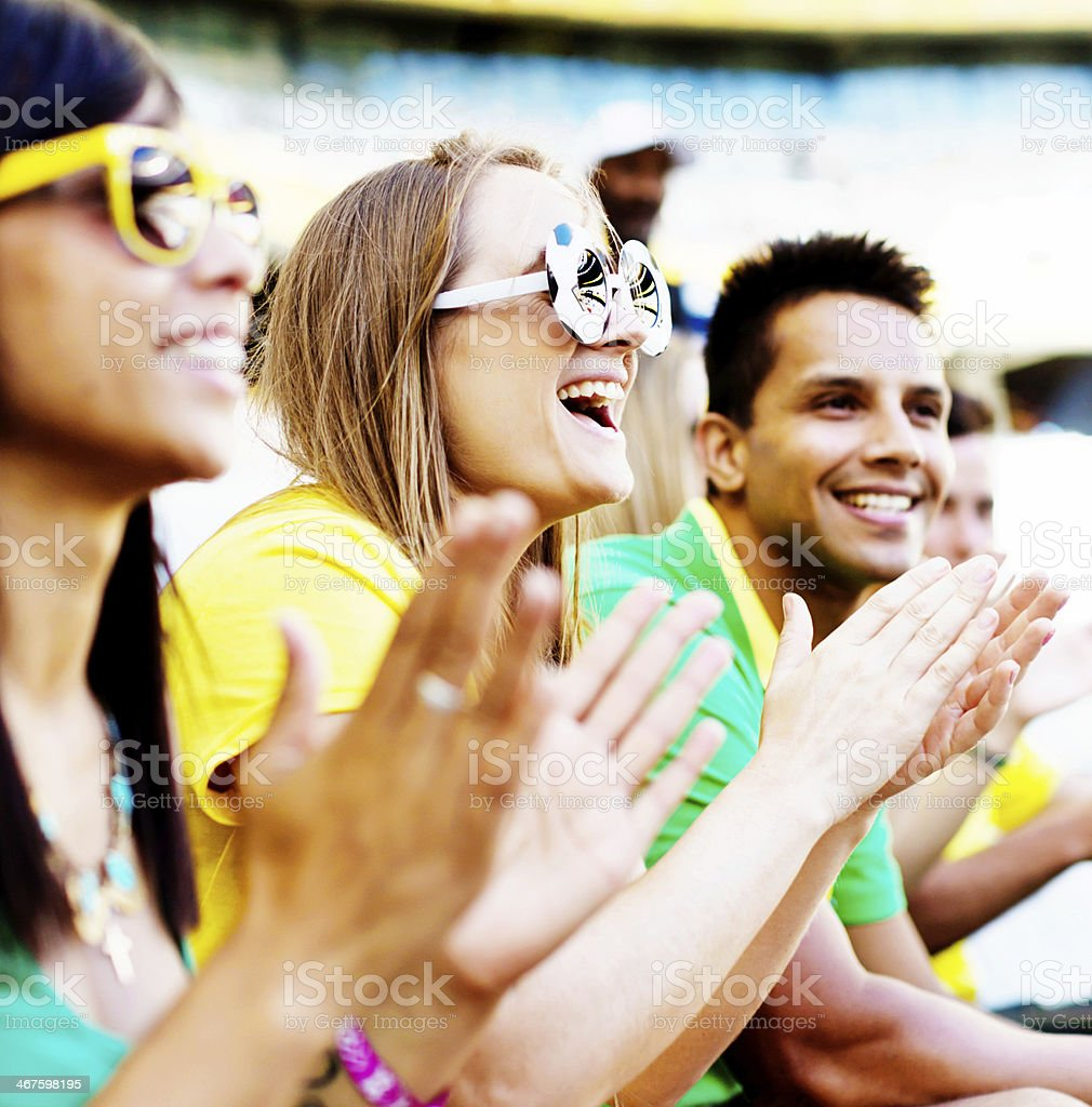 Applauding soccer fans in Brazilian team colors at football match stock photo